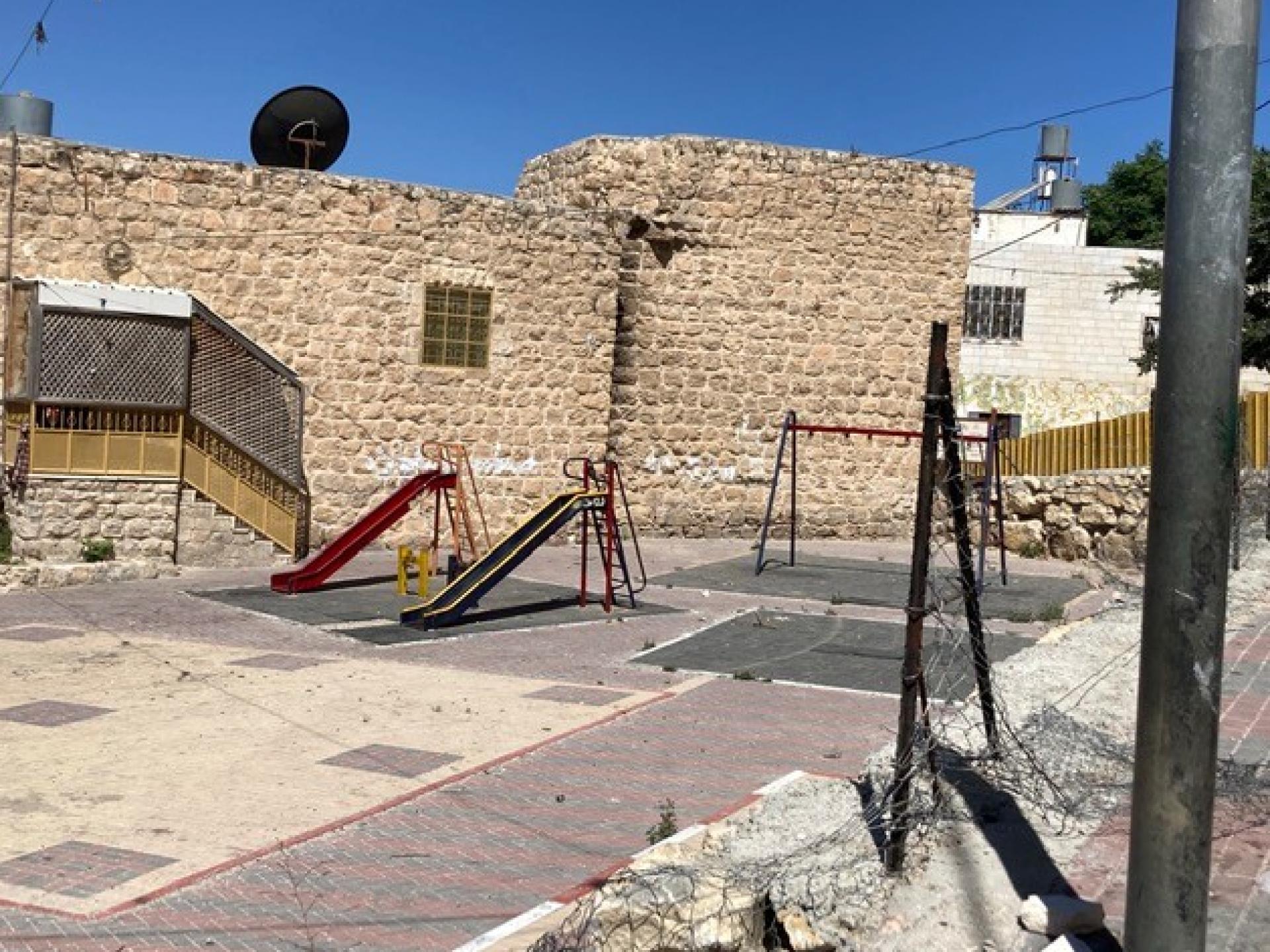 מבנה אבן עם מגלשות ונדנדה בחצרו