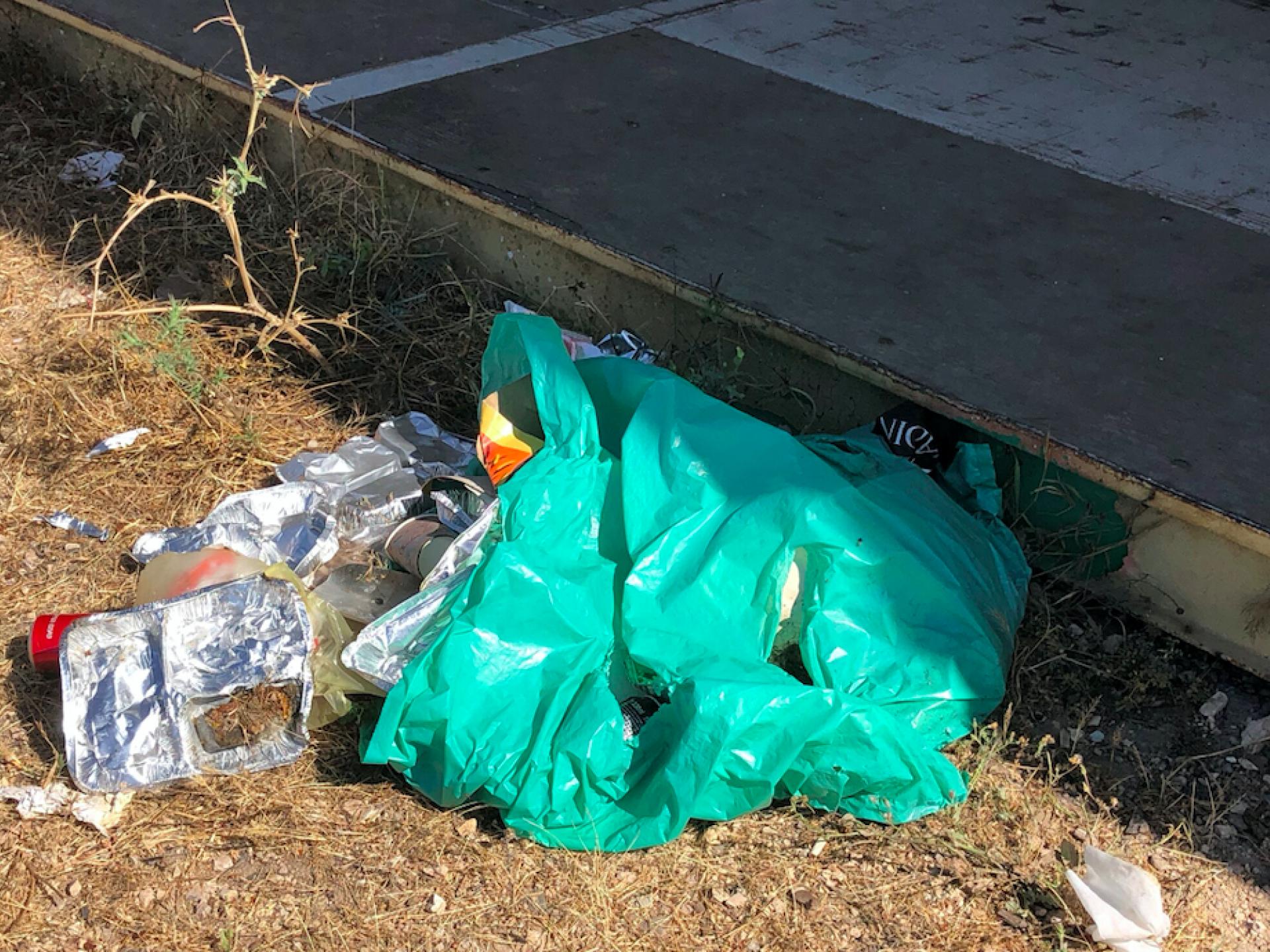 שקית אשפה זרוקה על האדמה עם פסולת מארוחת צהריים של החיילים נשפכת מתוכה