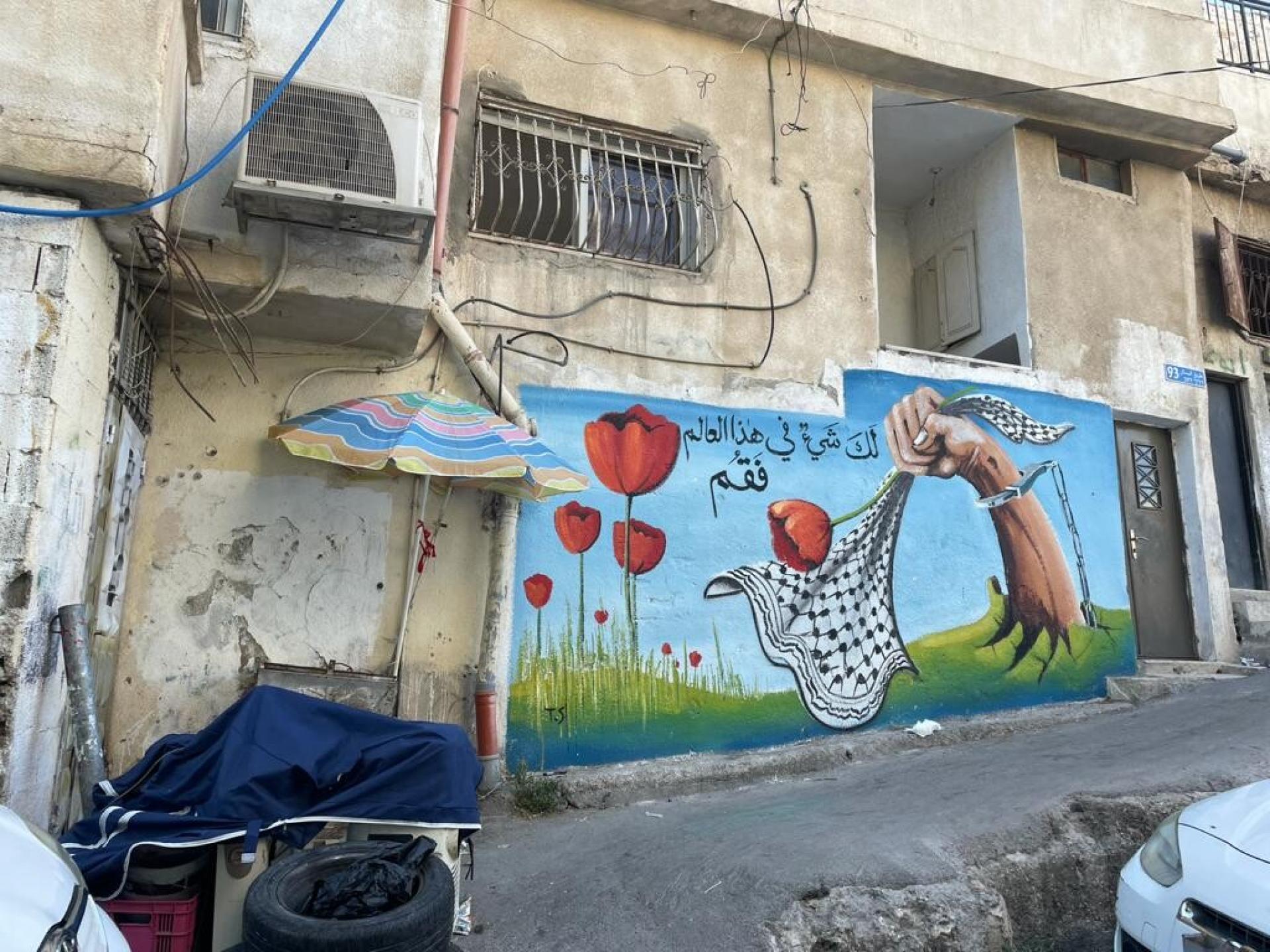 גרפיטי על קיר בית בשכונת הבוסתן, תמונת יד כבולה בשלשלאות מגיחה מן האדמה ואוחזת בכפייה ופרח פרג אדום