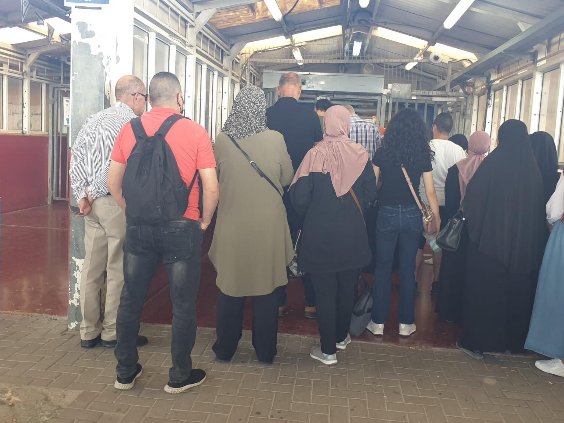 קבוצת פלסטינים ממתינים בתור בתוך מחסום