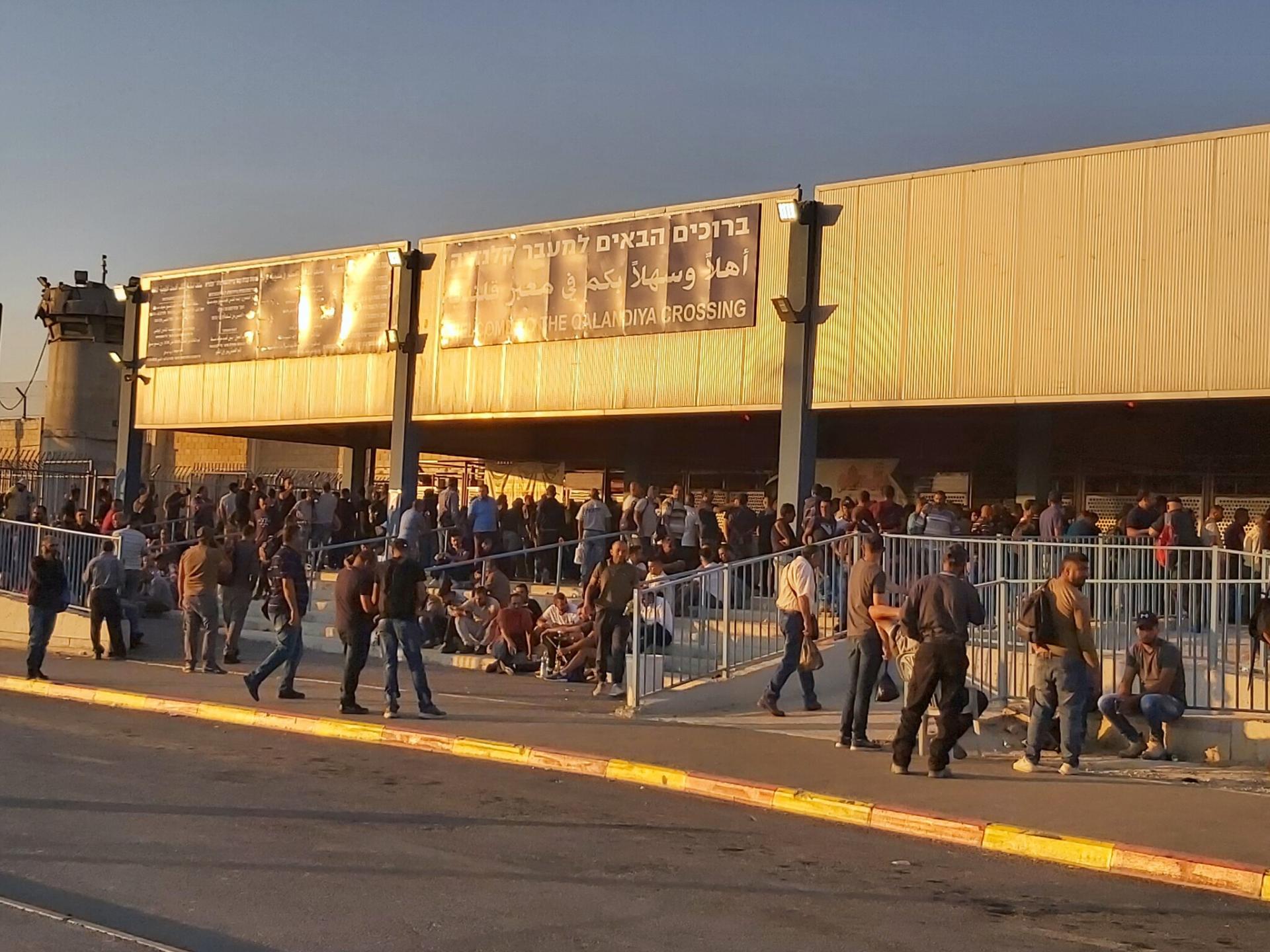 אנשים רבים מתחת לסככה בכניסה למחסום