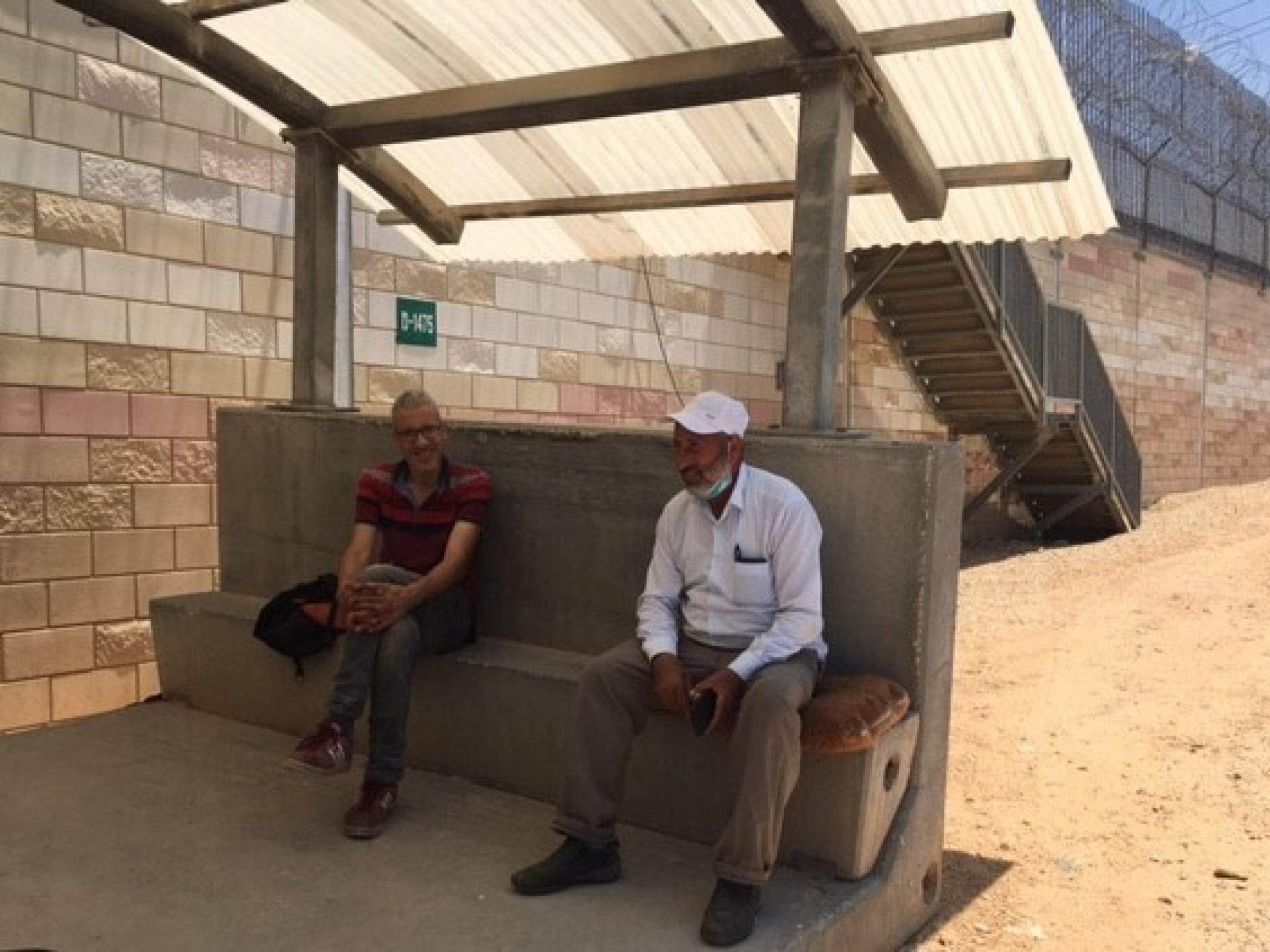 שני גברים מחכים בצל לפתיחת המחסום