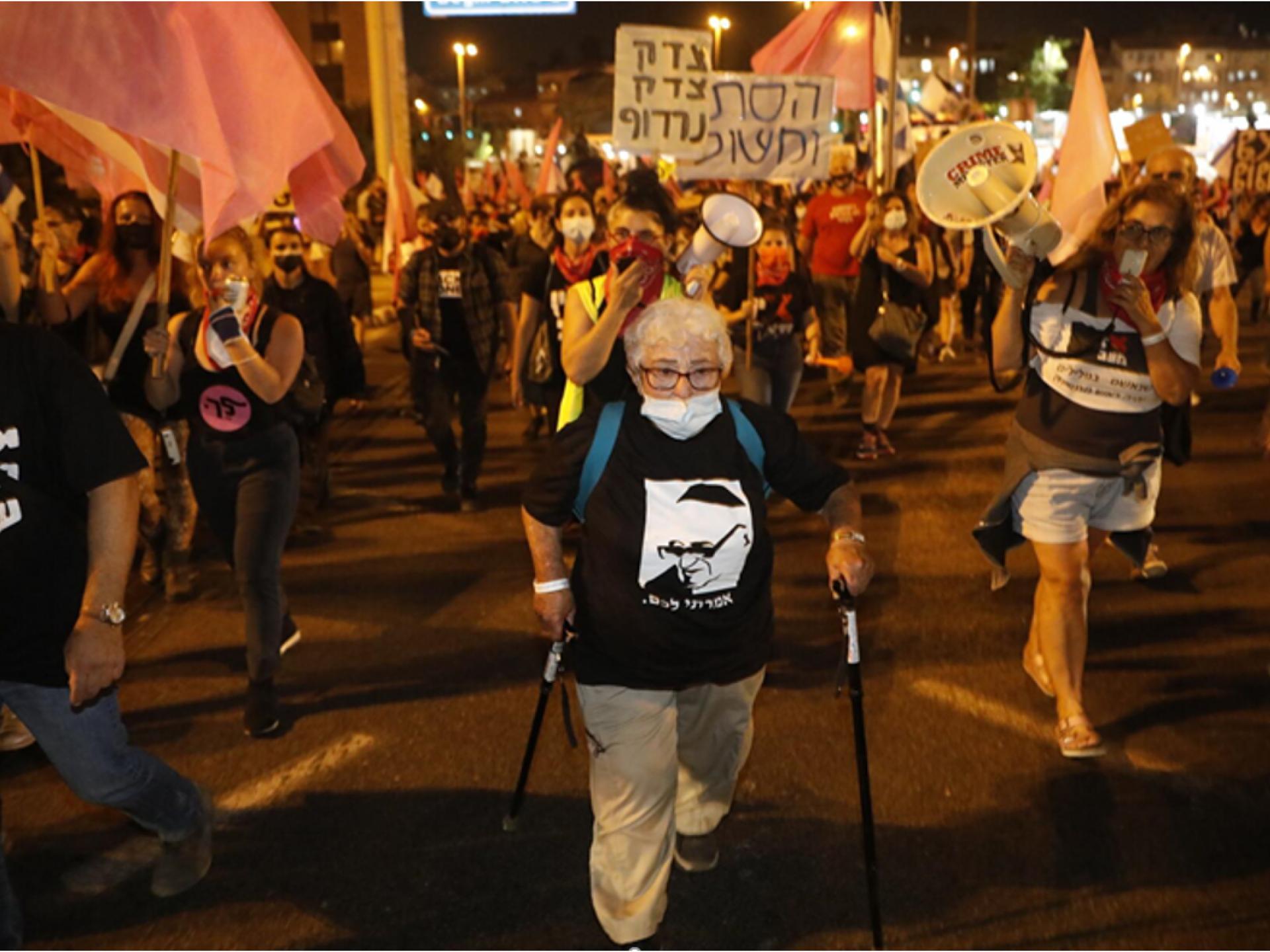 אישה מבוגרת עם מקלות הליכה מפינה עם קבוצת צעירים