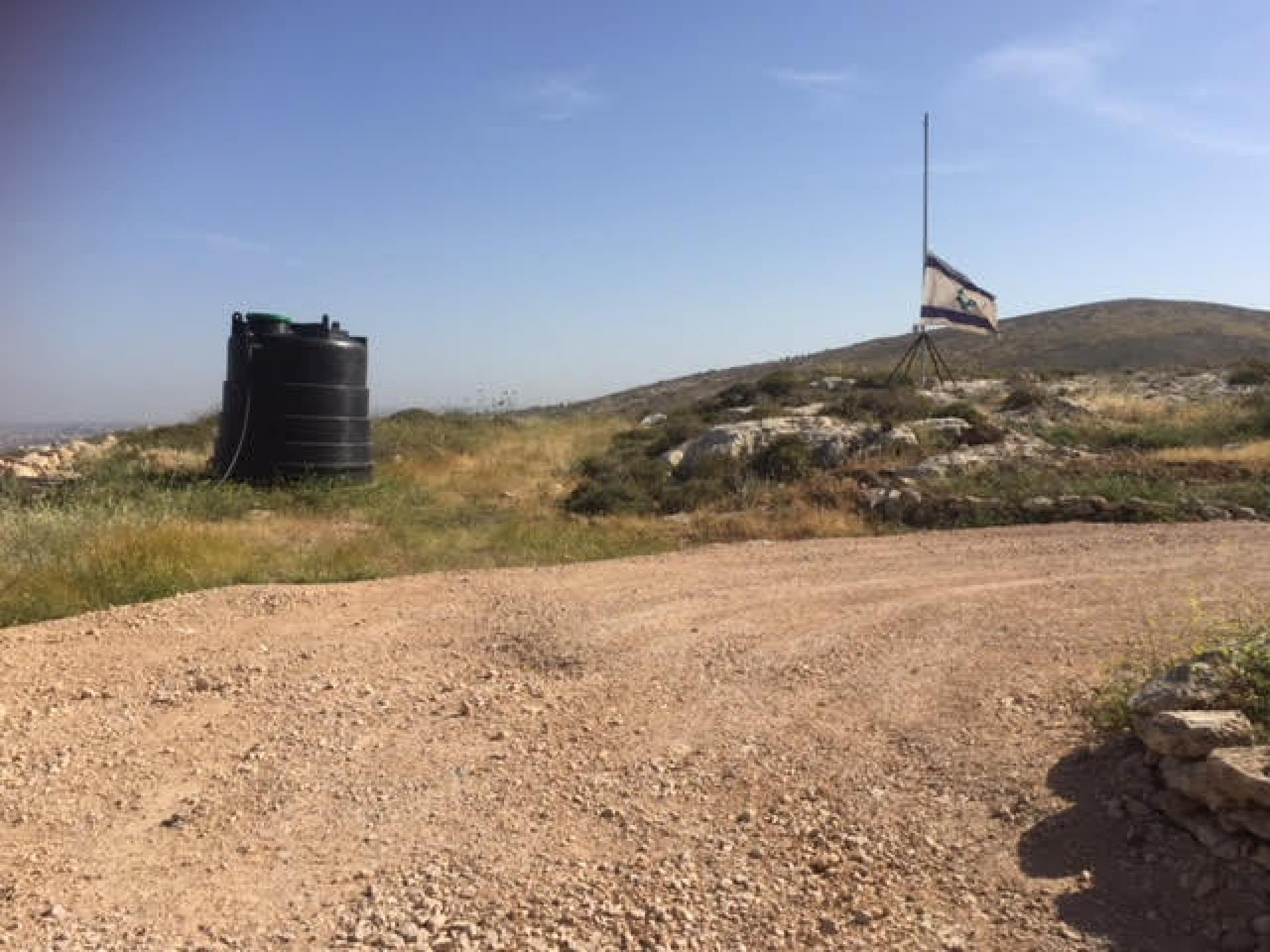 The flag and water tank on another hill, closer to the main road and to the settler-colony