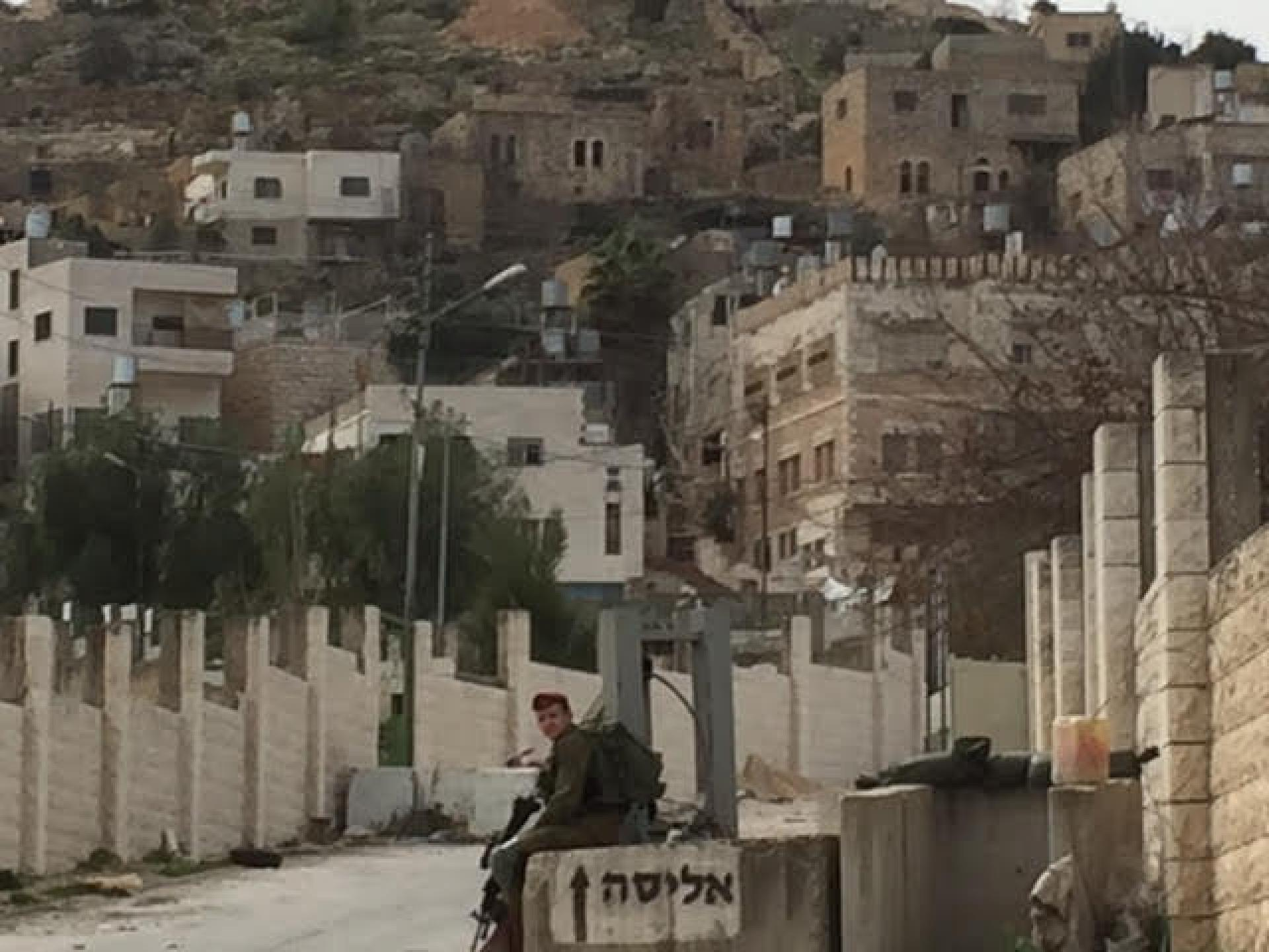 חייל שומר על כיכר גרוס פתחו את השער לשכונת אבו סנאן