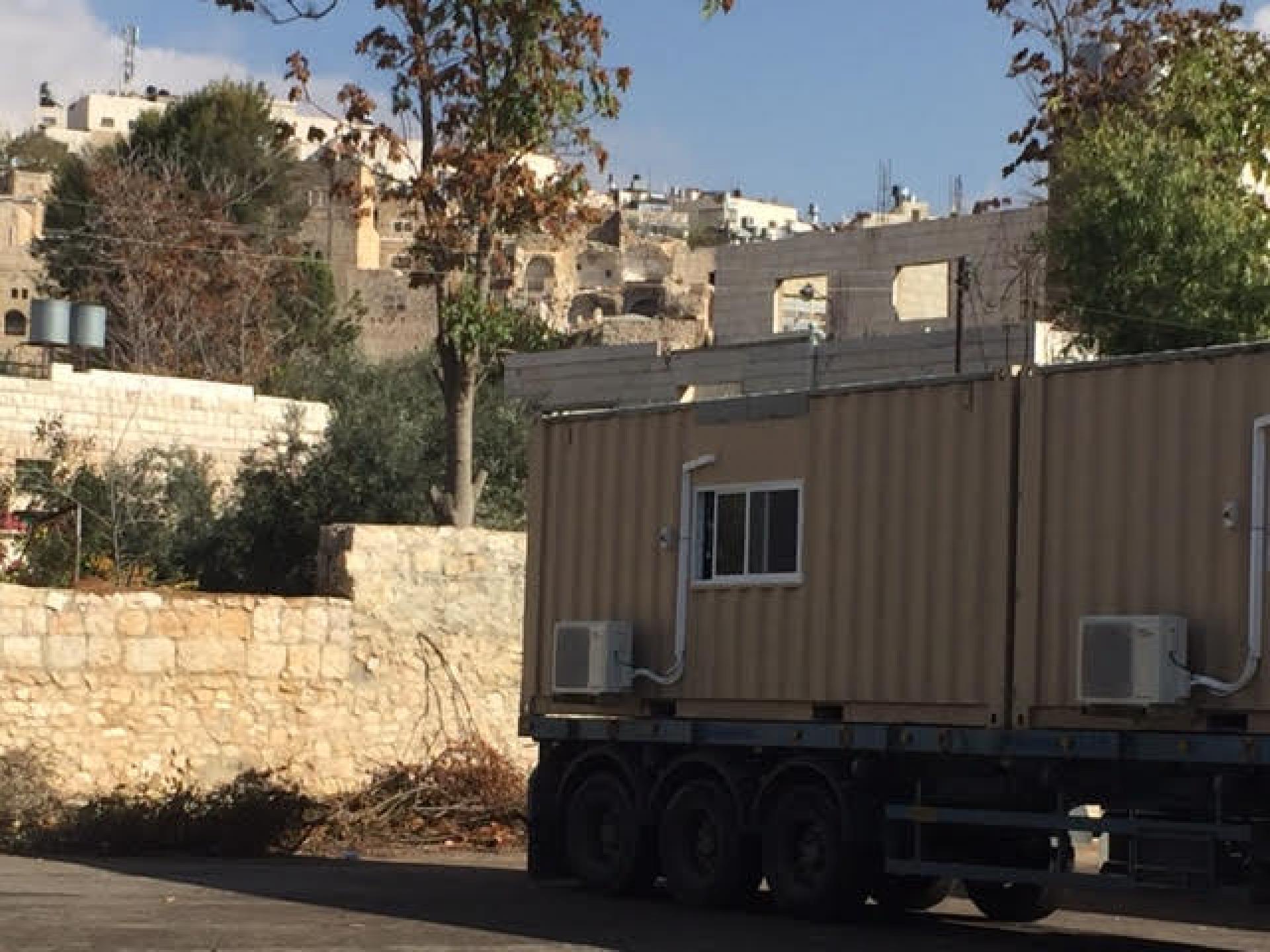 מכונית צבאית נוסעת לשם עם שלושה מבנים יבילים