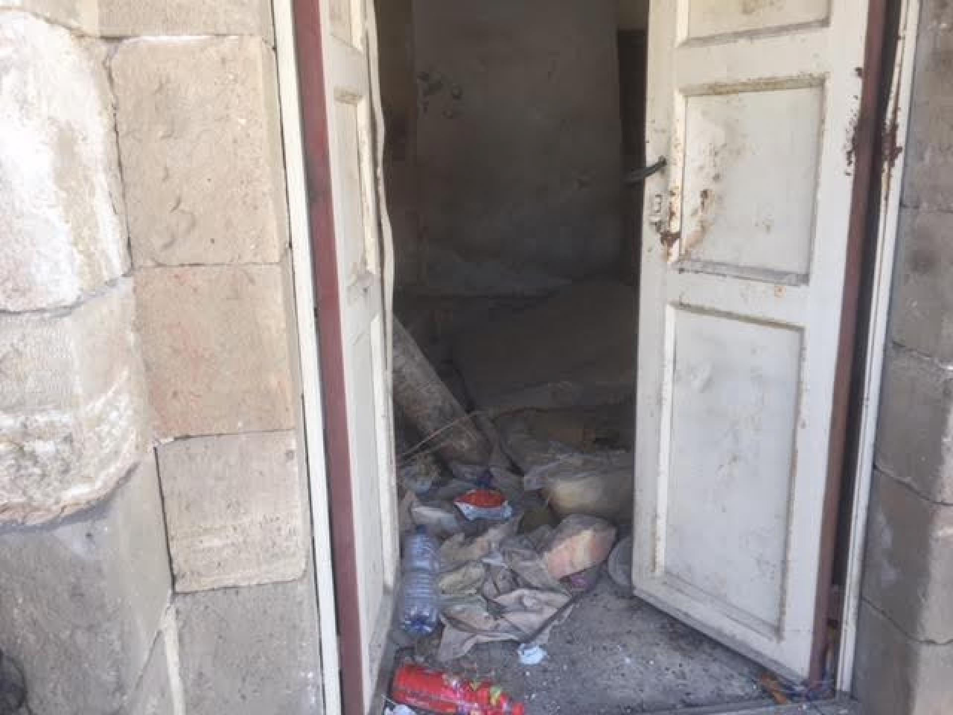 The first house in Shuhada street. The door which had been  welded is open