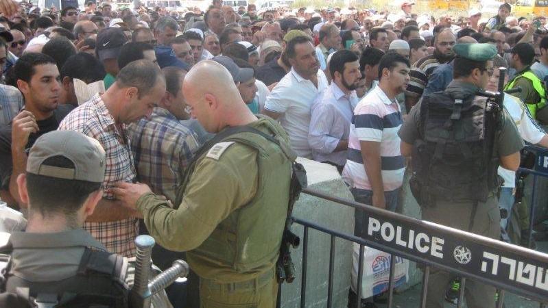 חייל בודק ממסמכים ומאחוריו המון רב של אנשים