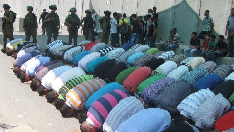 מוסלמים מתפללים וחיילים עומדים לצידם