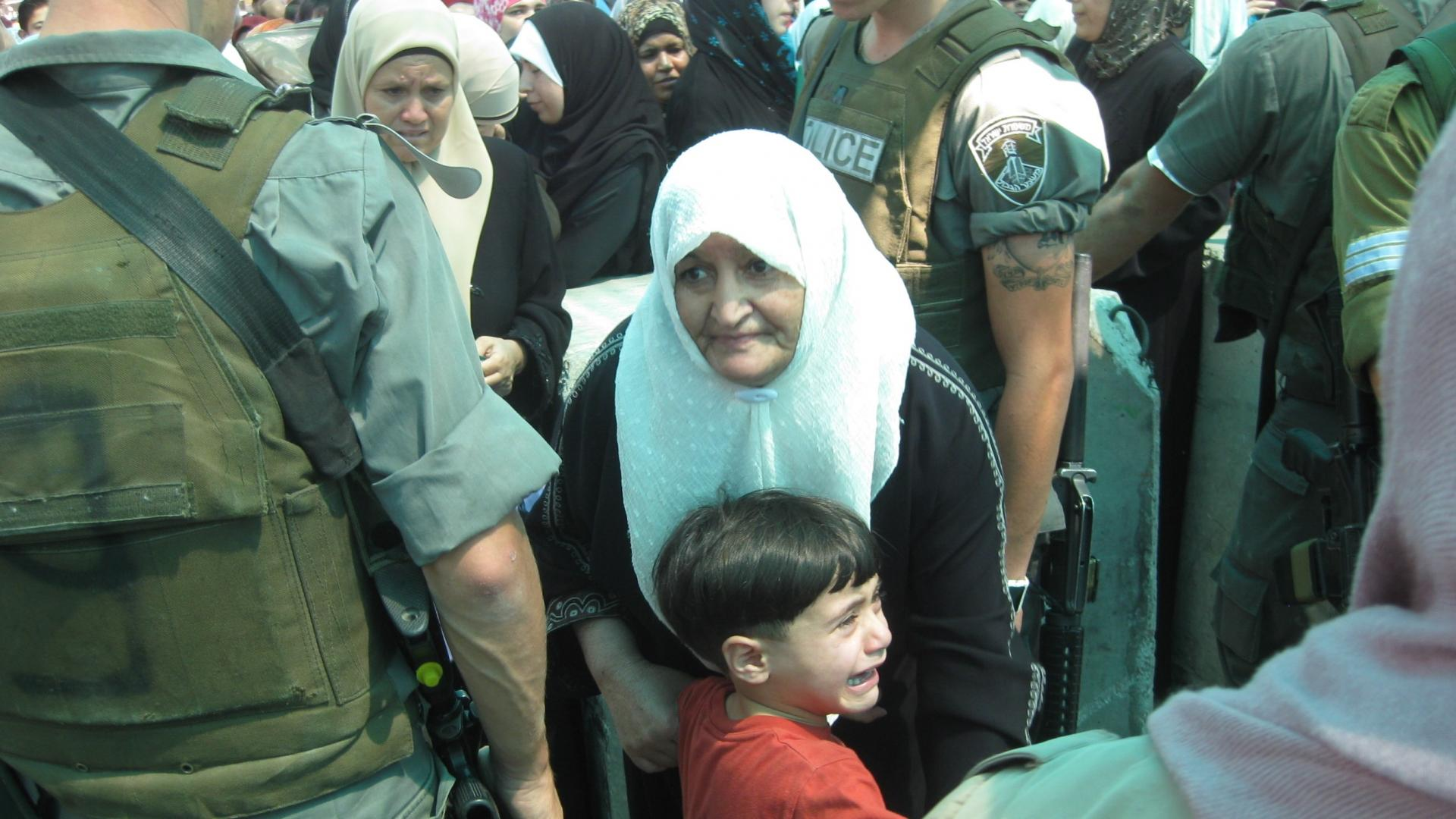 An older woman; a child crying; a soldier at the checkpoint