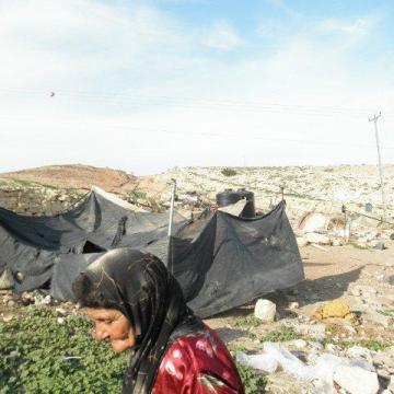 אישה עם מטפחת ליד אוהל הרוס