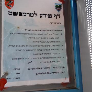דף מידע לטרמפיסט בתחנת האוטובוס בכניסה לבית פוריכ