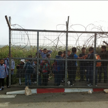 Children on their way to school are waiting for the sleeve to open to cross the checkpoint.