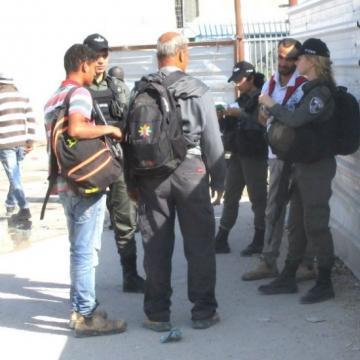 שלושה שוטרי מגב בודקים אישורים מחוץ למחסום