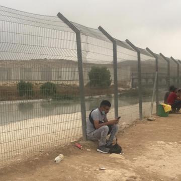 פלסטינים יושבים על גדות נחל הביוב ומחכים להסעה