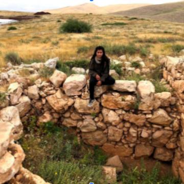 נערה יושבת על שפת בור מדופן באבנים
