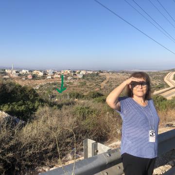 אישה מצילה על עיניה מהשמש. ברקה גדר ההפרדה וכפר פלסטיני. יש סימון של שער שבגדר