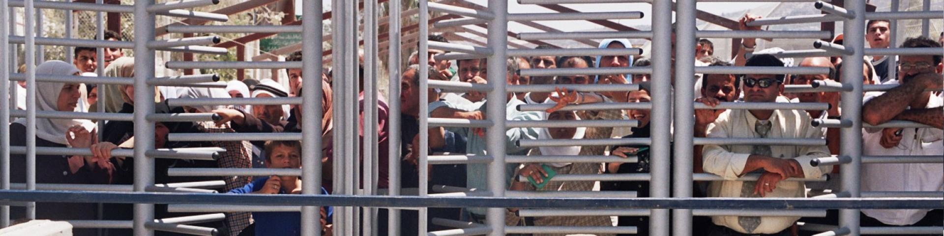 פלסטנים מעבר לסורגי המחסומים בדרך לישראל